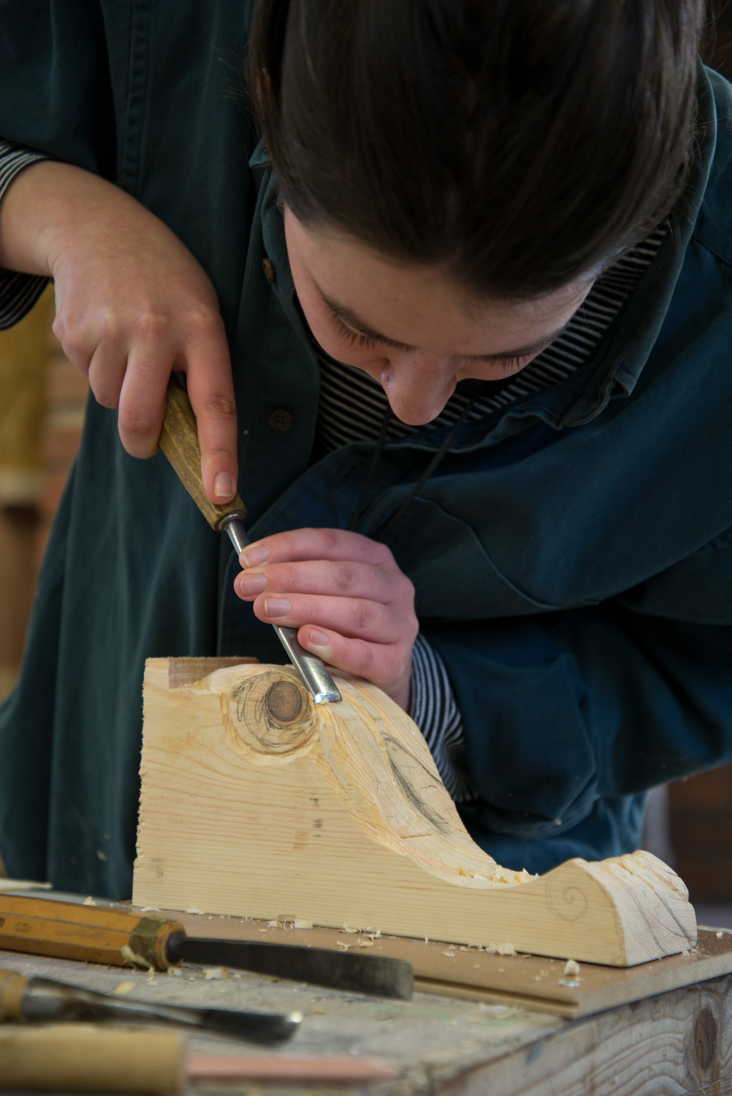 Image of a woman carving a piece of wood