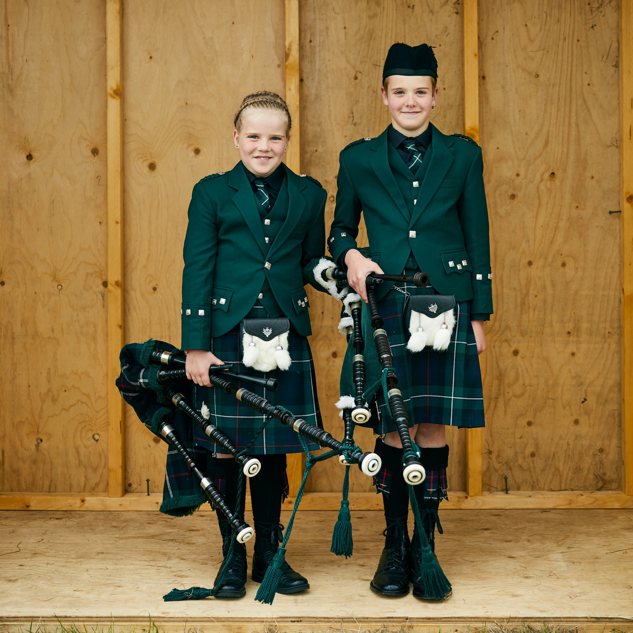 Image of two girls wearing kilts and holding bag pipes