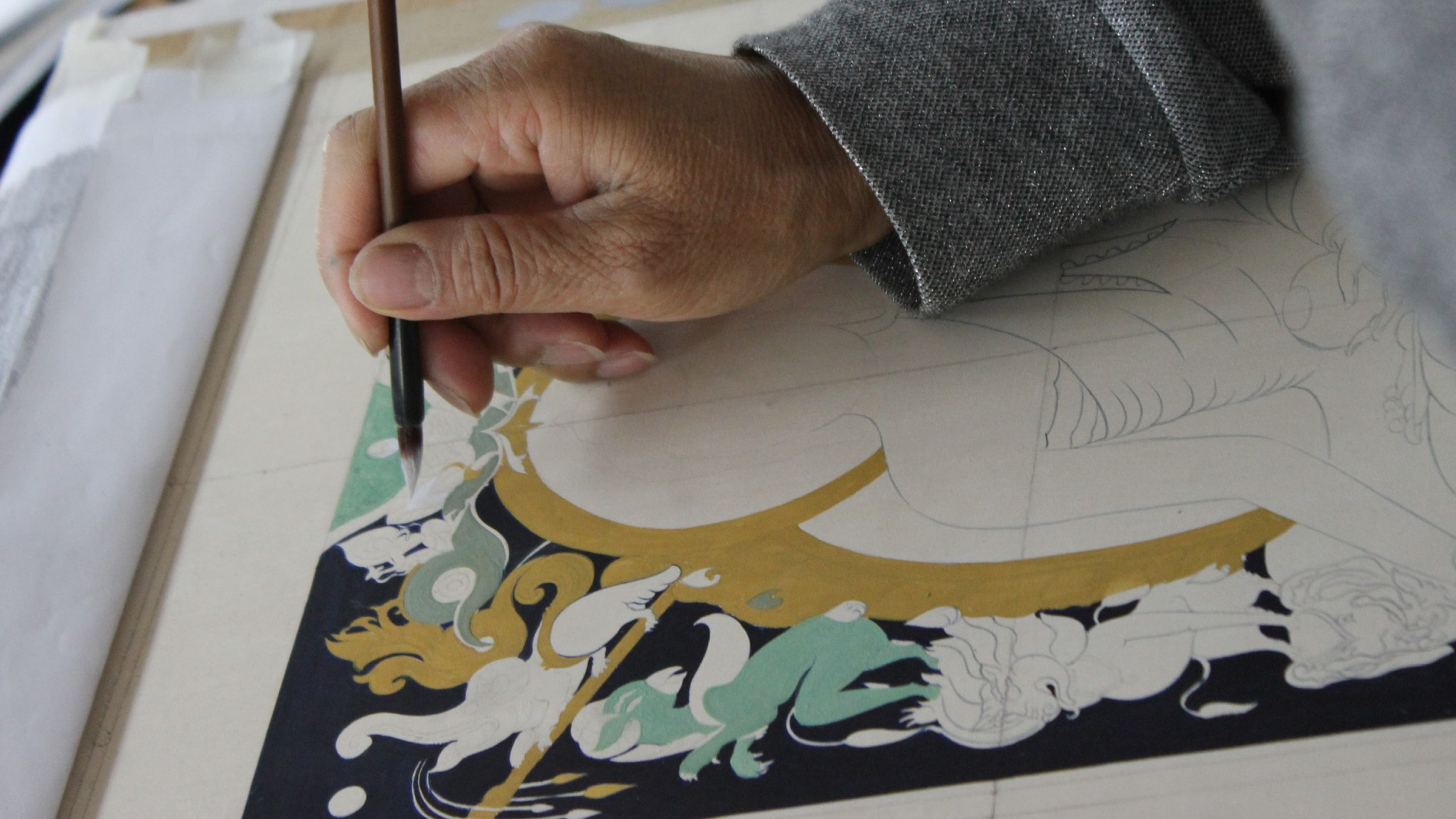 Image of a student painting with a traditional brush