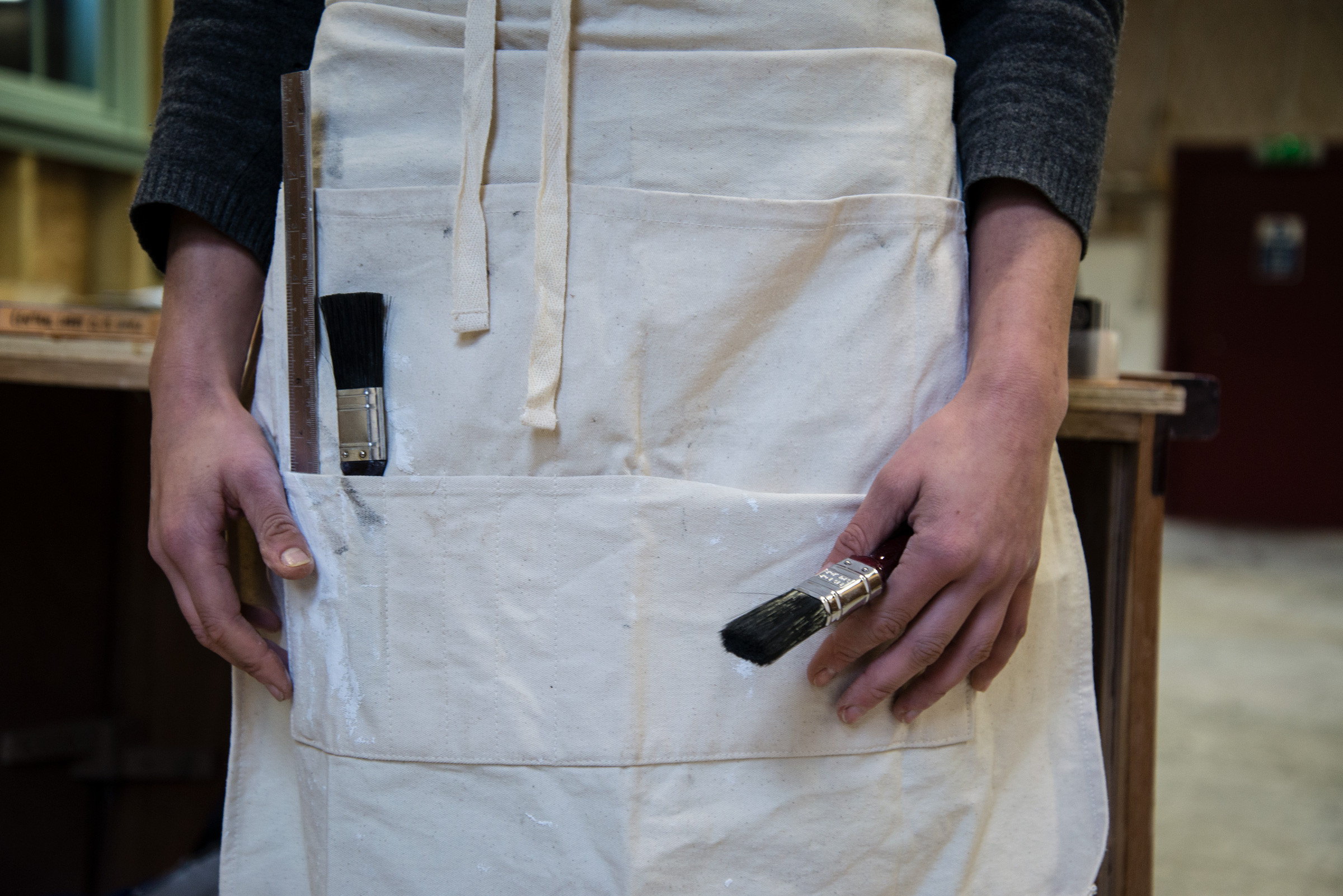 Image of a man wearing a apron and holding a pencil