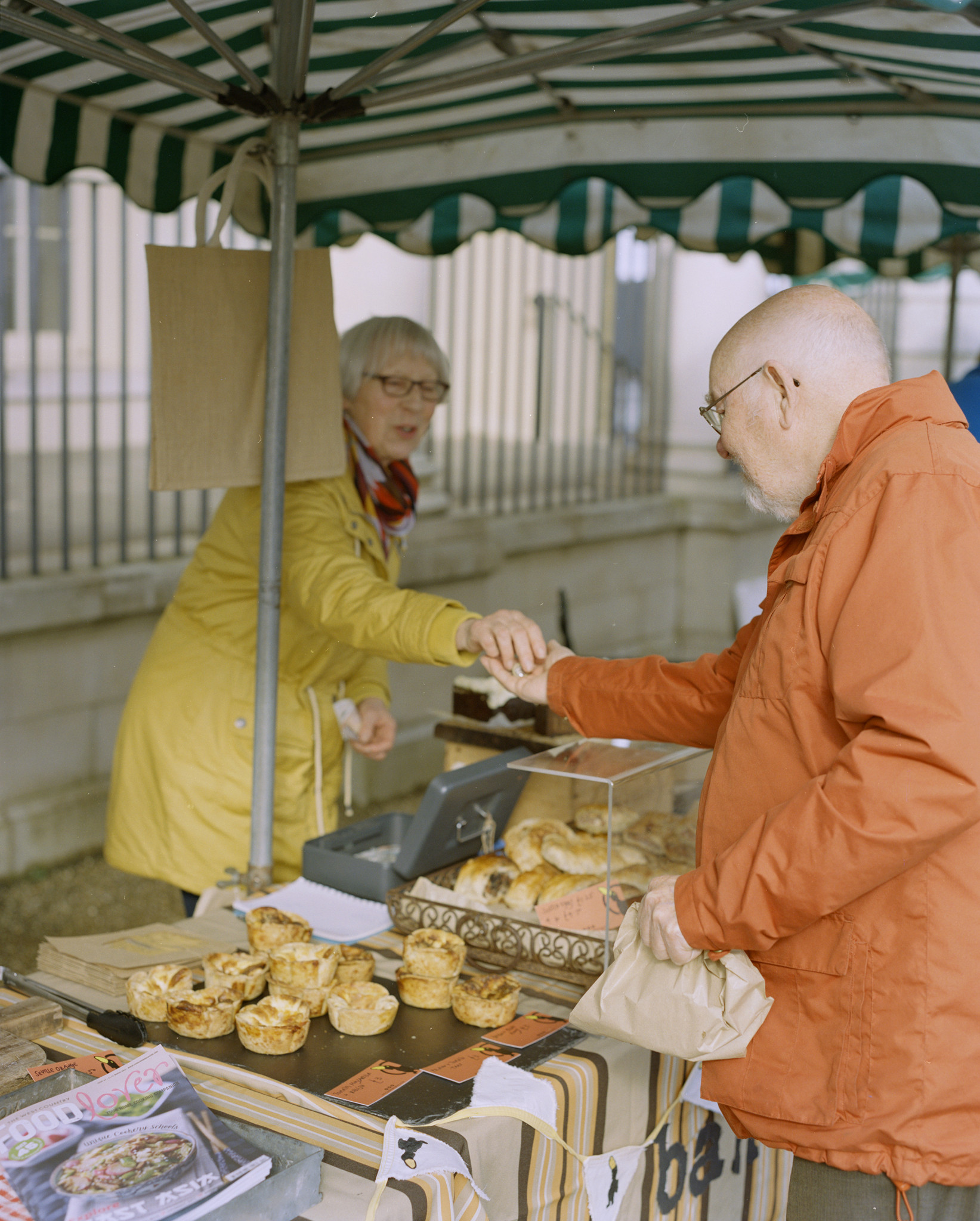 Image of man buying pastry from a woman in a market stall