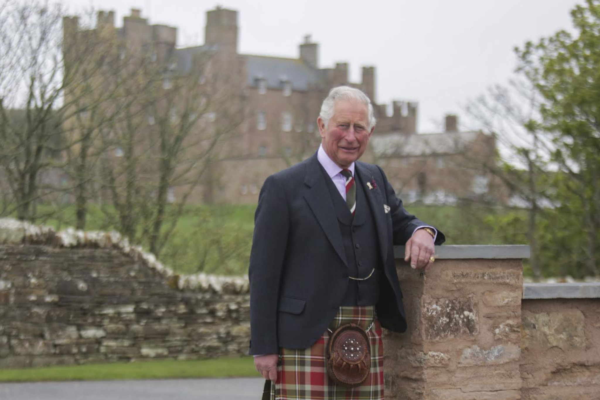 Image of HRH Prince Charles wearing a kilt with the castle of mey in the distance