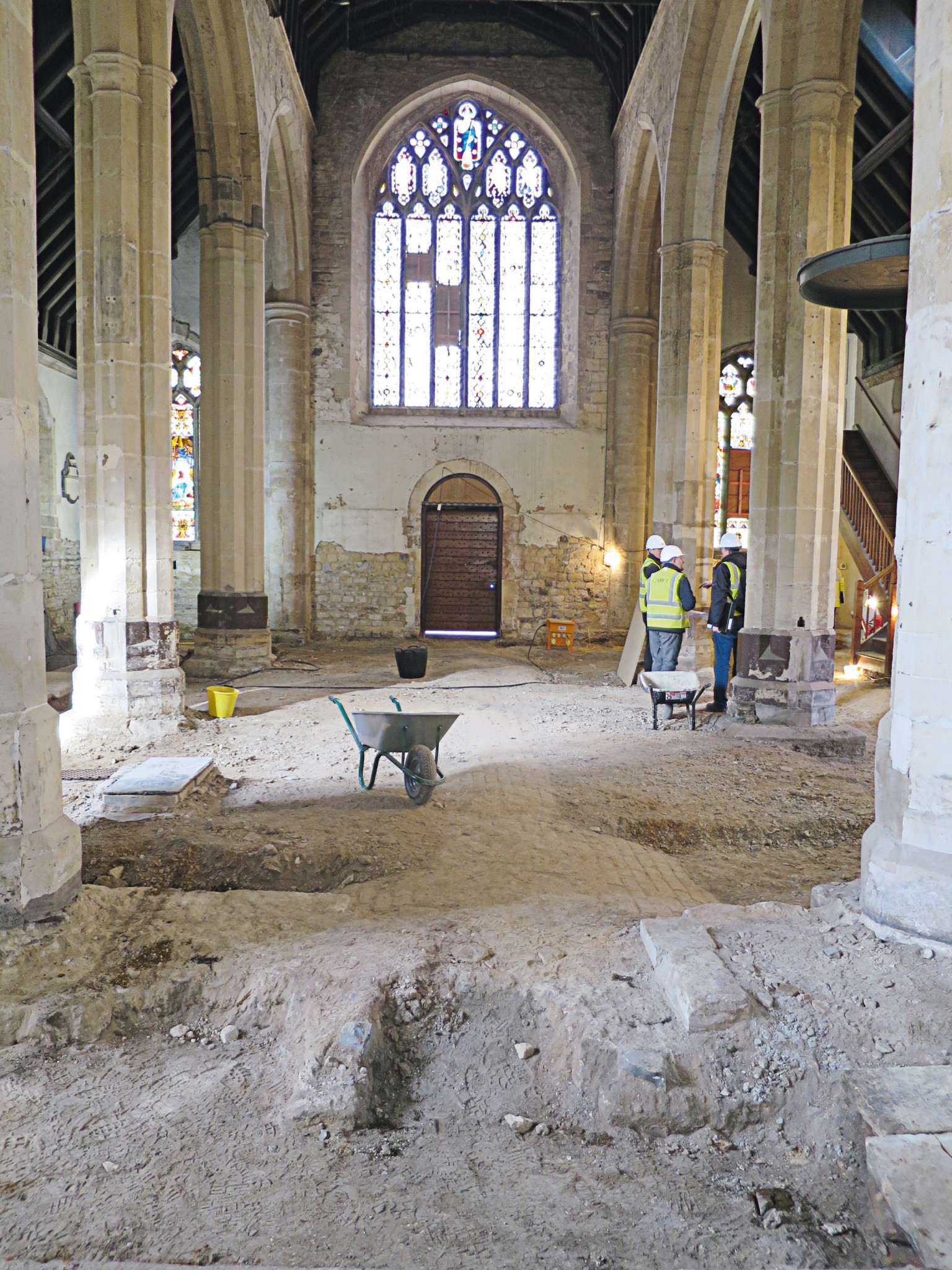 Image of the church interior with three builders talking