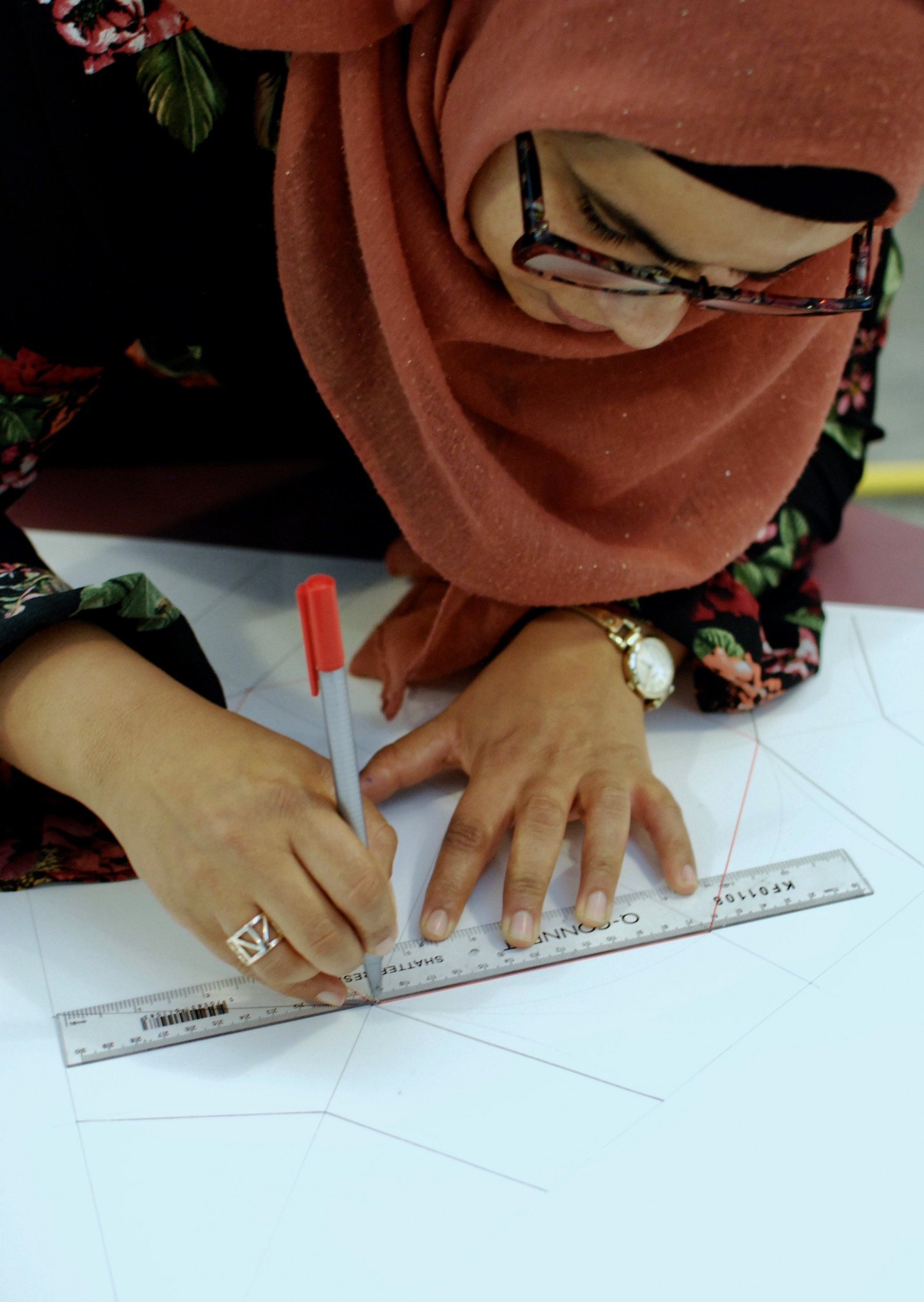 A photo of woman drawing using a ruler