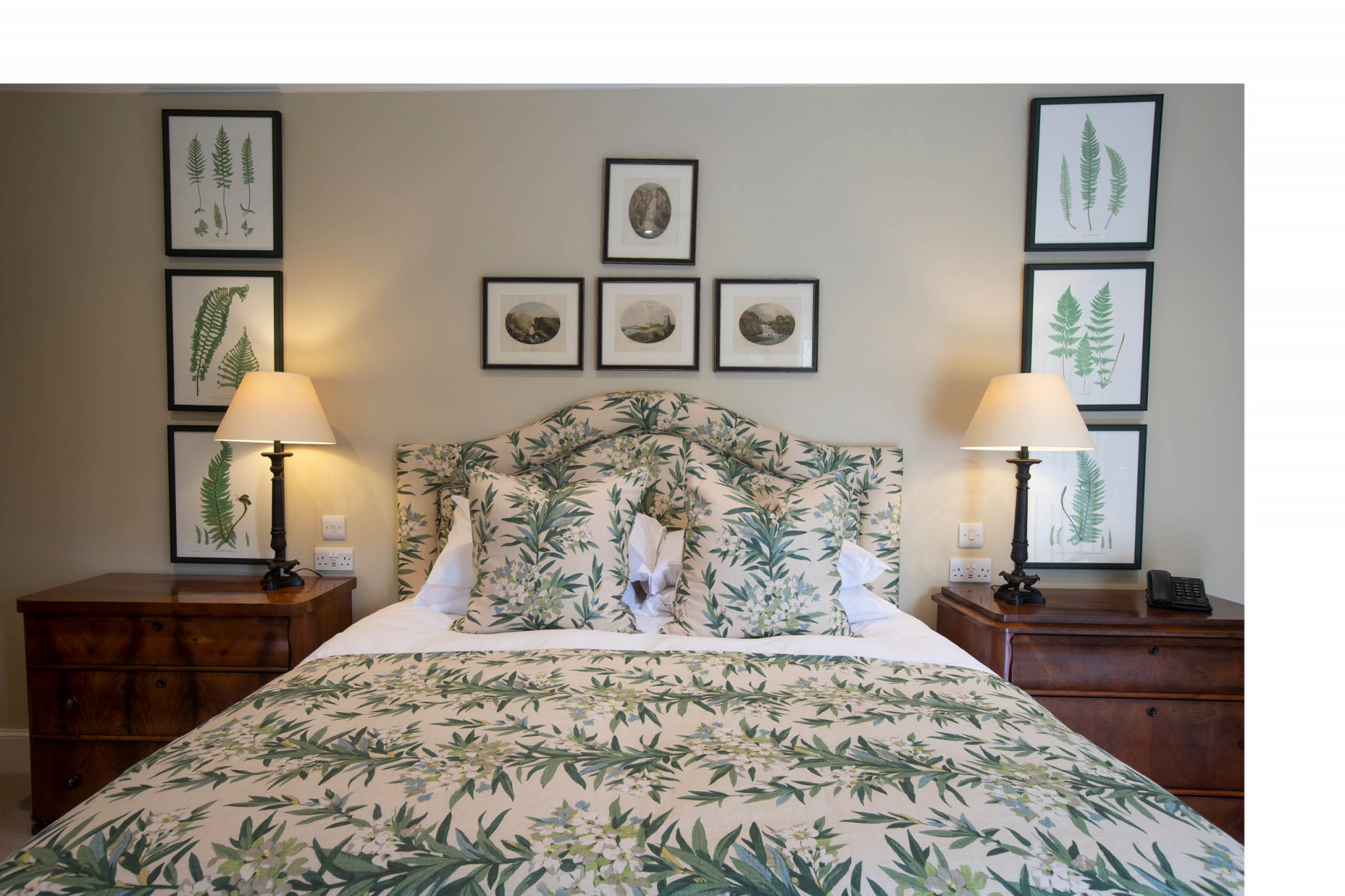Image of a bedroom with bedding, bed frame and pictures of different leaves