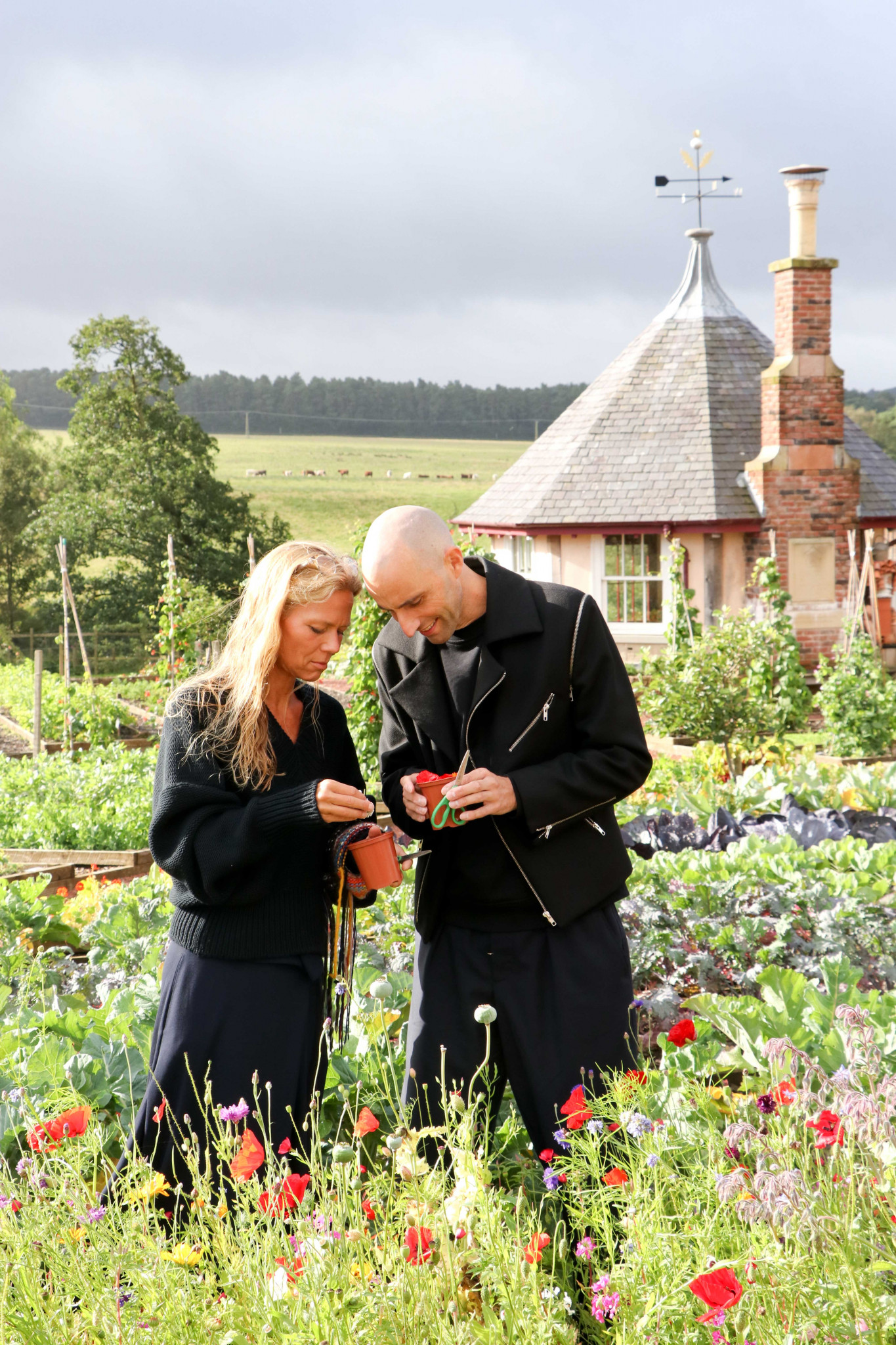 A man and a women standing in a garden looking at flowers